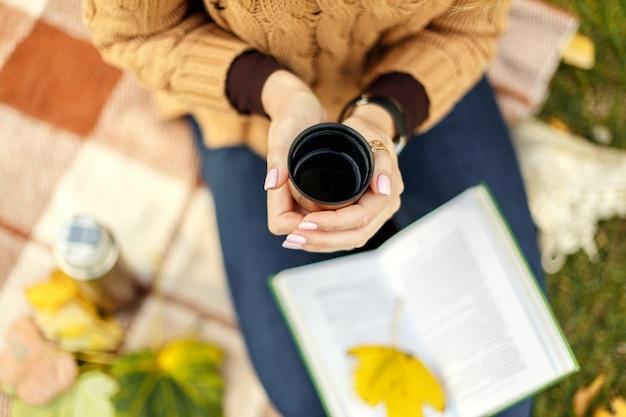 Tenant une tasse de thé chaud dans un parc en automne