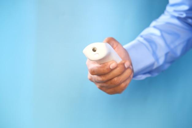 Tenant un thermomètre infrarouge pour mesurer la température contre le mur bleu