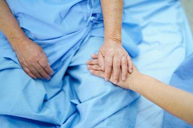 Tenant toucher les mains asiatiques patiente senior avec amour.