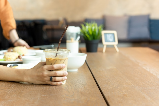 Tenant un verre de café au lait glacé avec de la nourriture sur la table à l'heure du déjeuner.