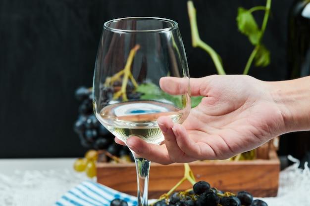 Tenant un verre de vin blanc dans la main.