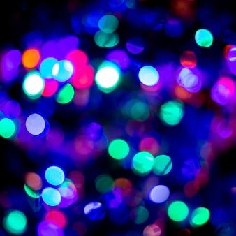 Tendance en 2021 noël ou nouvel an bokeh festif bleu et violet sur fond noir. toile de fond ou fonds d'écran.