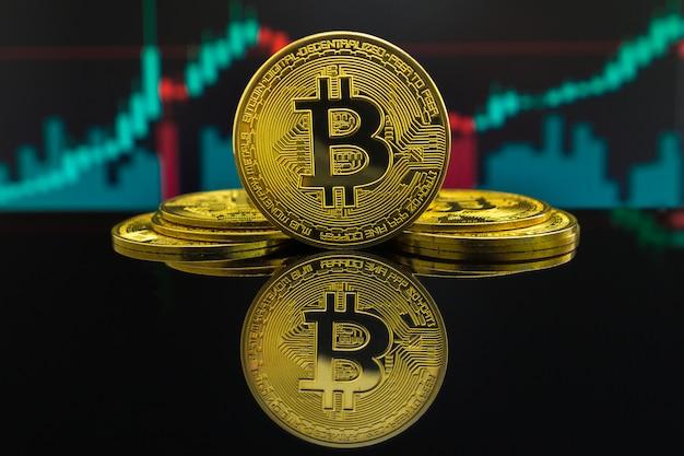 Tendance à la hausse et à la baisse de la crypto-monnaie bitcoin indiquée par des bougies vertes et rouges. pièce de monnaie btc devant le graphique de négociation