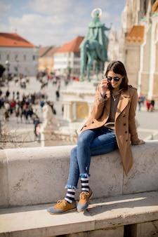 Tendance jeune femme assise en plein air et à l'aide de téléphone portable