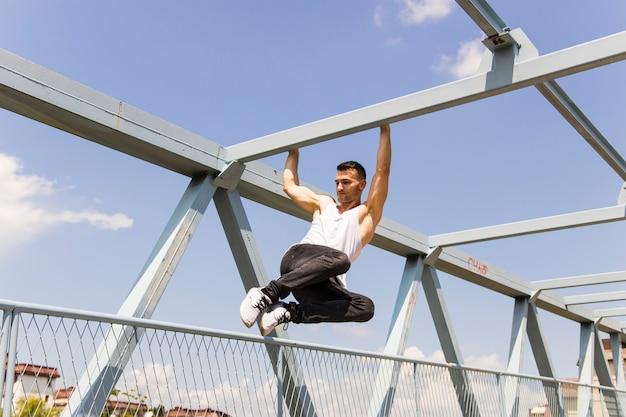 Tendance jeune homme accroché sur la tige de pont