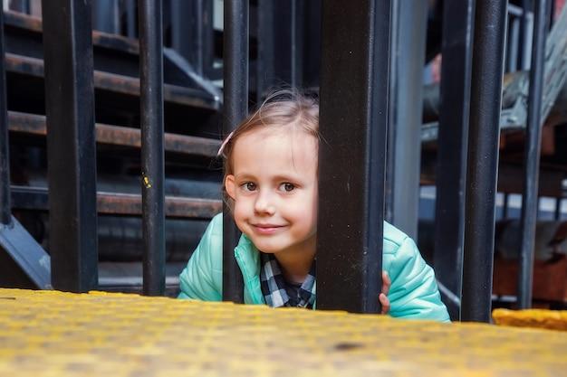 Tendance mignonne petite fille blonde caucasienne posant en regardant la caméra sur l'escalier en fer