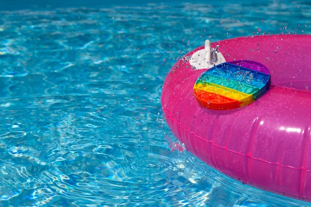 Tendance pop it fidget jouet et fragment anneau gonflable dans la piscine jour d'été éclaboussure d'eau
