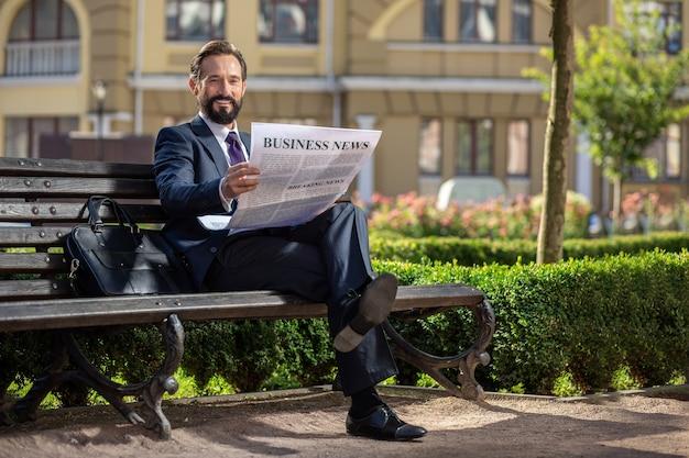 Tendances commerciales. sur toute la longueur d'un homme d'affaires confiant souriant, lisant un journal alors qu'il était assis sur le banc