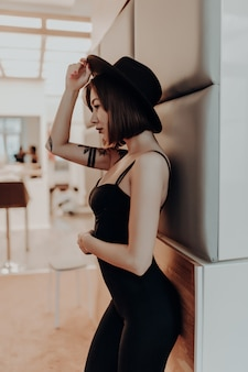 Tender woman adult brunette woman in black dress and hat standing near the wall in luxury apartment