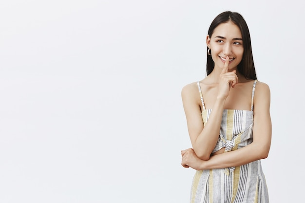 Tendre et attrayante jeune femme en haut et short assortis, souriant sensuellement, ayant un excellent plan, disant chut, faisant un geste chut avec le doigt sur la bouche