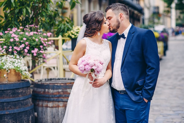Tendre baiser de superbe couple de mariage debout à l'extérieur