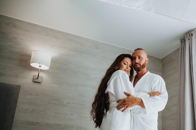 Tendre et un beau jeune couple amoureux en peignoirs blancs dans l'hôtel de luxe ou la chambre se tiennent debout et s'embrassent. heureux ensemble