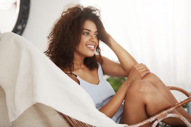 Tendre belle femme africaine en vêtements de nuit souriant assis sur une chaise au repos se détendre à la maison.