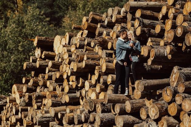 Tendre couple amoureux embrassant, sentiments de bonheur et souriant sur les bûches abattues dans la forêt.