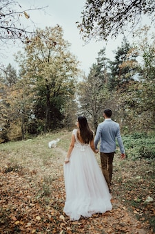Tendre couple de mariage amoureux dans la forêt d'automne avec un chien marche