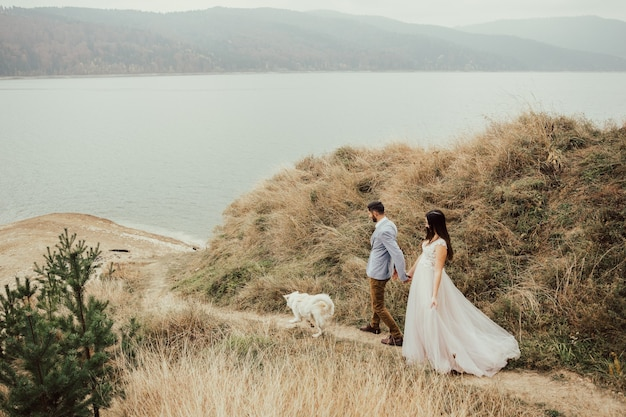 Tendre couple de mariage amoureux dans la forêt d'automne avec un chien se promène près du lac