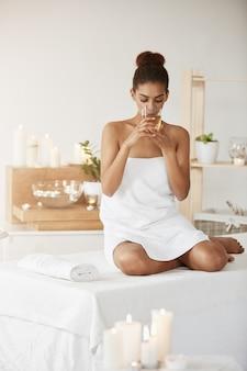 Tendre femme africaine, boire du thé vert au repos dans le salon spa.