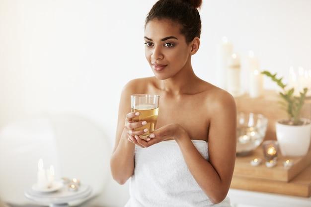 Tendre femme africaine souriante tenant le verre avec du thé se détendre dans le salon spa.