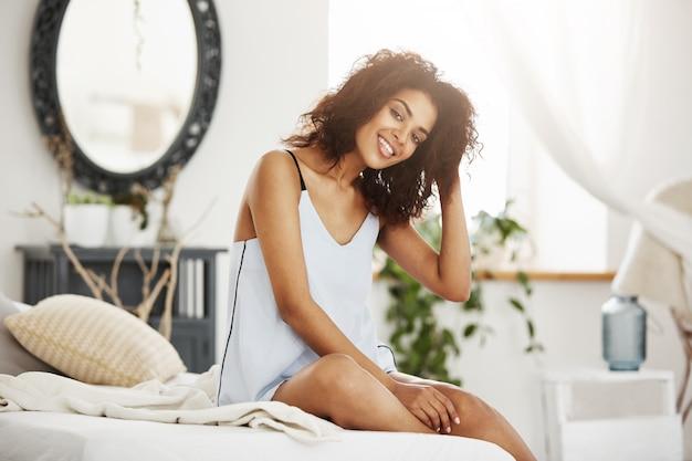 Tendre femme africaine en vêtements de nuit assis sur le lit à la maison en souriant.