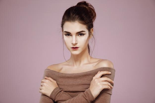 Tendre femme posant avec les bras croisés sur rose