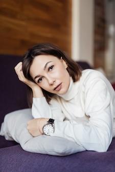 Tendre femme se détend sur le lit à la maison après étude