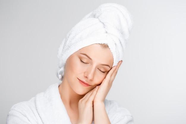 Tendre femme souriante touchant le visage propre