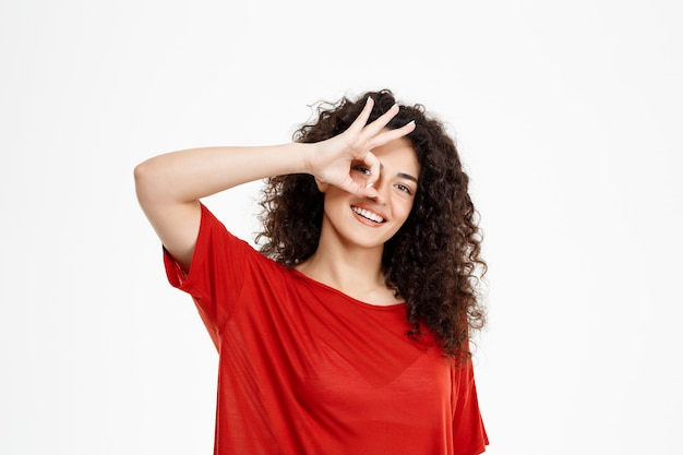 Tendre fille bouclée souriant et pointant signe ok