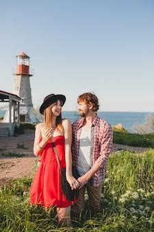 Tendre jeune couple élégant amoureux dans la campagne, style bohème indie hipster, vacances de week-end, tenue d'été, robe rouge, herbe verte, main dans la main, souriant