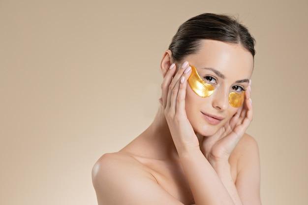 Tendre jeune femme aux épaules nues utilisant des plaques dorées sous les yeux. isolé sur fond de studio beige. concept de beauté et de soins de la peau.