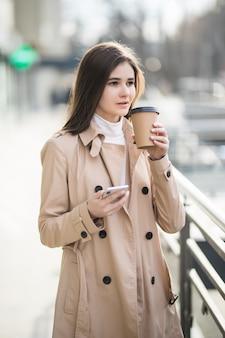 Tendre jeune femme boit du café dans sa propre tasse à l'extérieur