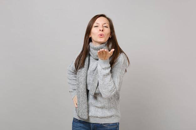 Tendre jeune femme en écharpe pull gris soufflant envoyant un baiser d'air isolé sur fond de mur gris en studio. les gens de mode de vie sain émotions sincères concept de saison froide. maquette de l'espace de copie.