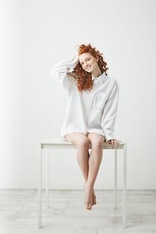Tendre jeune femme rousse en chemise assise sur la table souriant à corriger les cheveux.
