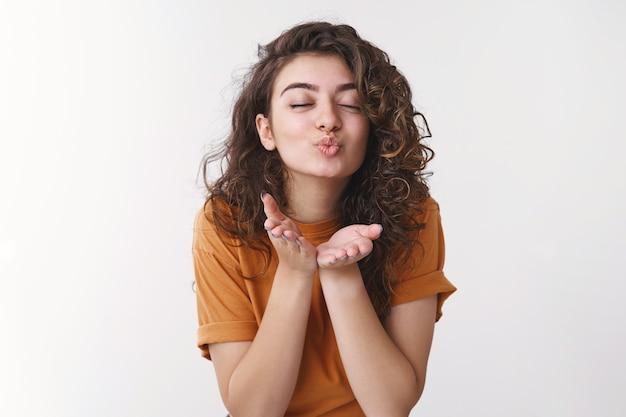 Tendre jeune fille arménienne passionnée passionnée aux cheveux bouclés yeux fermés léger sourire pur envoyer des baisers d'air caméra pli lèvres donner mwah amour tout le monde debout fond blanc romantique humeur flirty
