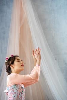 La tendre jeune fille à l'image d'une princesse en robe rose avec une couronne sur la tête ferma les yeux et tendit les bras.