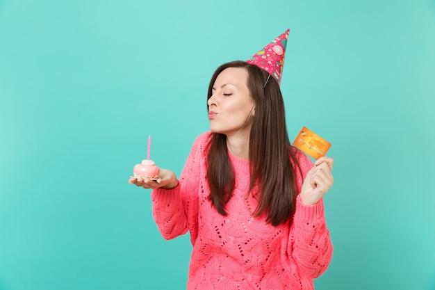 Tendre jeune fille en pull rose tricoté, chapeau d'anniversaire avec les yeux fermés soufflant la bougie sur le gâteau, tenir en main une carte de crédit isolée sur fond bleu. concept de mode de vie des gens. maquette de l'espace de copie.