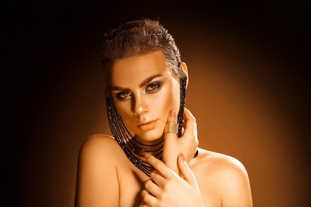 Tendre jeune fille avec un sking sain et un maquillage professionnel de couleurs vertes. tourné en studio. fond orange