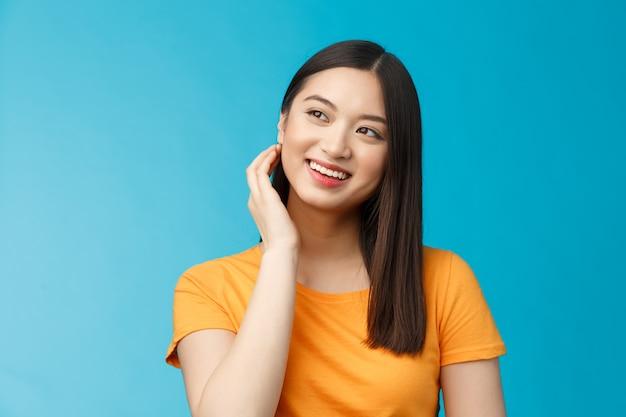 Tendre jolie femme asiatique moderne et coquette touche les cheveux, regarde de côté, sourit joyeusement, se sent satisfaite après une bonne coupe de cheveux, traite les boutons désagréables, se débarrasse de l'acné ravie, se tient sur fond bleu.
