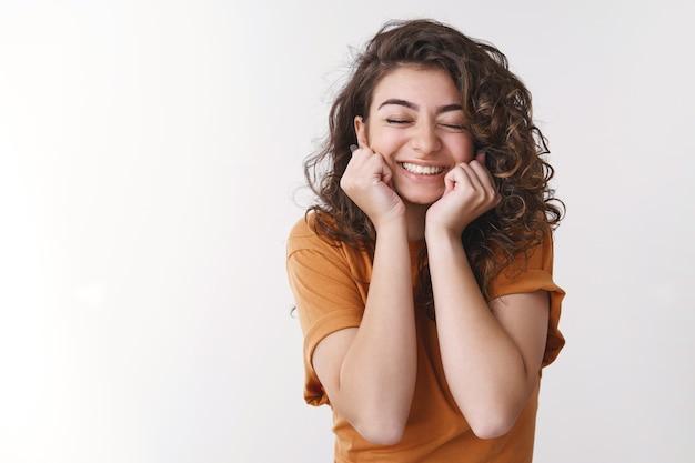 Tendre jolie fille féminine excitée camarade de classe invitée au bal de promo souriant joyeusement rêve devenu réalité debout touché passionnément yeux fermés acclamant joyeusement la presse mains joues, fond blanc