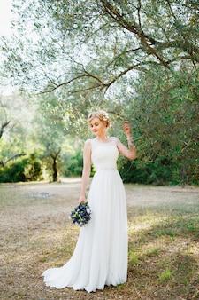 Une tendre mariée avec un bouquet de fleurs bleues se tient près d'un olivier et touche les branches avec