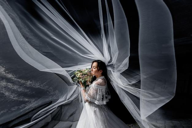 Tendre mariée avec bouquet de mariée dans les rayons du soleil avec voile réparti