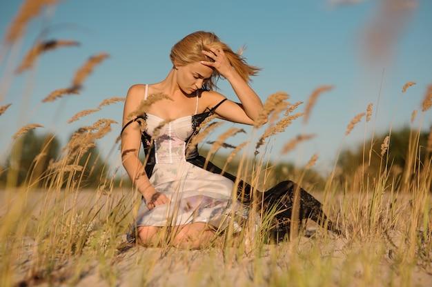 Tendre portrait d'une fille blonde dans une lingerie assise sur le terrain