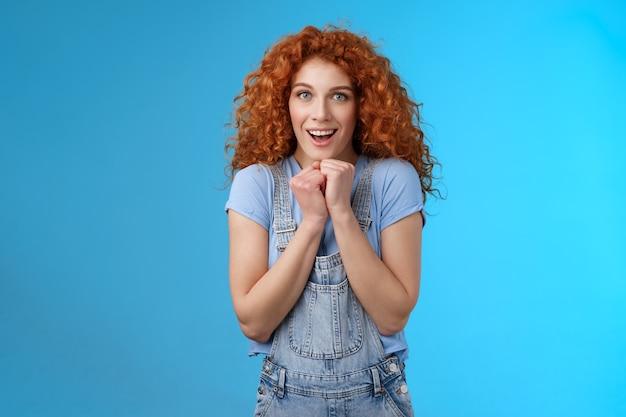 Tendre rousse sensible sensible émotive fille bouclée serrer les mains ensemble touché souriant haletant voir scène réconfortante belle caméra look chiot fasciné regard ravi impressionné fond bleu.