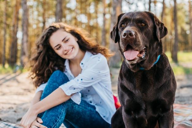 Tendre scène de fille heureuse avec son animal de compagnie dans la forêt