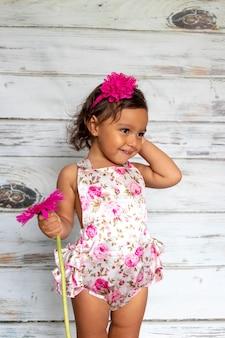 Tendre sourire d'enfant en bas âge, avec une fleur à la main
