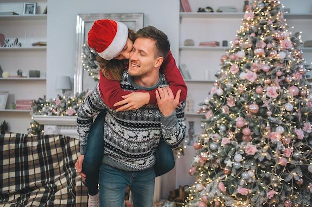 Tendre et touchante photo de jeune femme embrassant l'homme. elle s'assoit sur son dos et l'embrasse. ils passent du temps ensemble dans une salle décorée.
