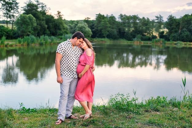 Tendres câlins de futurs parents sur fond de lac et forêt.