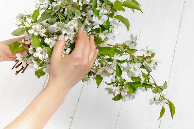 Tendresse des mains féminines avec des fleurs de printemps. concept de tendresse, soins de la peau, les mains de la jeune fille tiennent des fleurs de printemps
