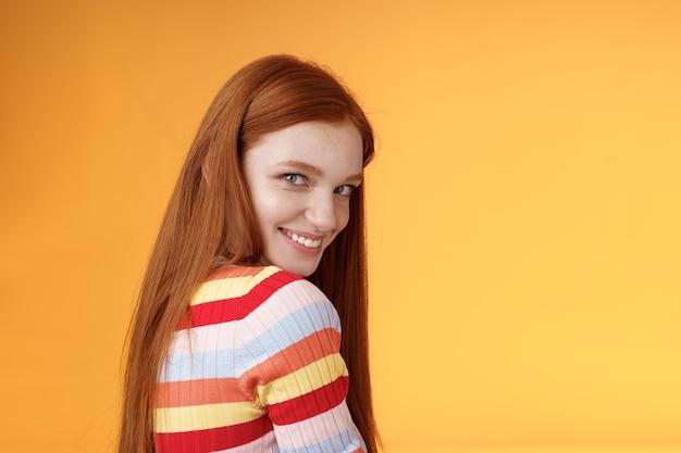 Tendresse, romance, concept de séduction. jolie jeune fille audacieuse rousse coquette et coquine se tourne derrière la caméra d'épaule de regard souriant rire coquette idiot exprimer l'affection de sympathie.