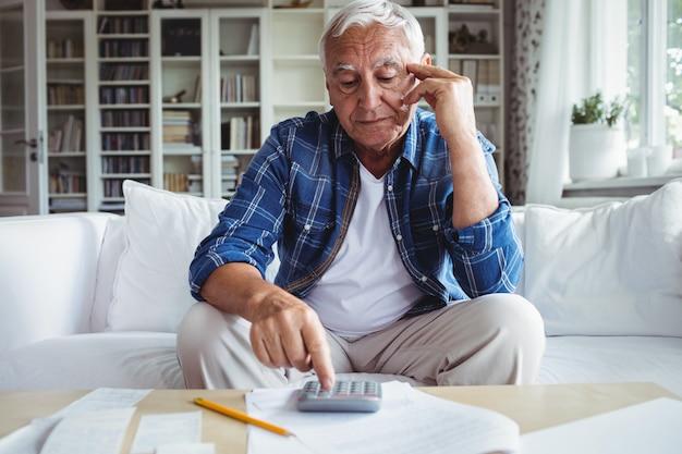 Tendu senior homme vérifiant les factures