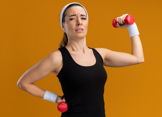 Tendue jeune fille assez sportive portant un bandeau et des bracelets tenant et soulevant des haltères en gardant la main sur la taille isolée sur un mur orange